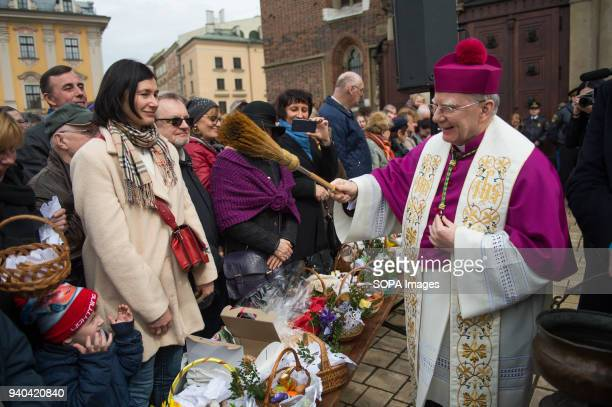 The Krakow archbishop Marek Jdraszewski blesses people easter baskets at the main square in Krakow Thousands of local gather in the main square of...