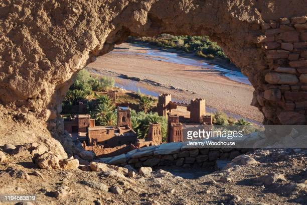 the ksar of ait ben haddou through a hole in the fortress wall - north africa stock pictures, royalty-free photos & images