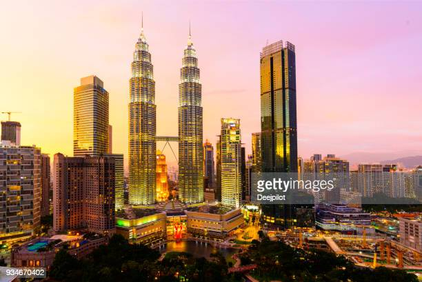 o skyline da cidade de kuala lumpur com as torres petronas iluminado ao pôr do sol, malásia. - torres petronas - fotografias e filmes do acervo