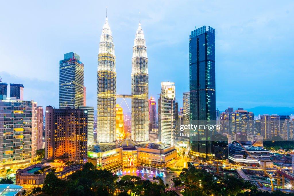 O Skyline da cidade de Kuala Lumpur com as torres Petronas iluminado ao pôr do sol, Malásia. : Foto de stock