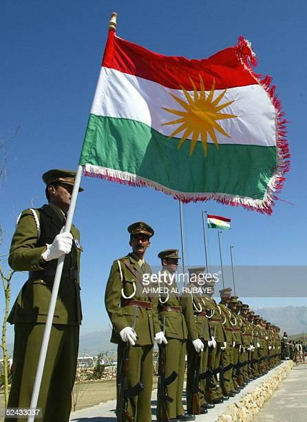 The Kurdish flag flutters as soldiers stand to attention during the anniversary ceremony at the memorial site of the 1988 victims of a gassing in the...