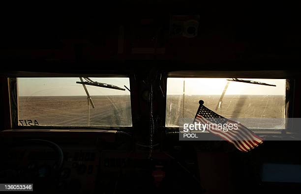 The Kuwaiti desert stretches beyond a US flag fluttering on the dashboard of a Mine Resistant Ambush Protected vehicle from the 3rd Brigade Combat...