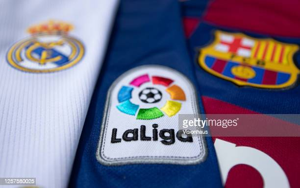 The La Liga logo with the FC Barcelona and Real Madrid club crests on the first team home shirts on July 22, 2020 in Manchester, United Kingdom.
