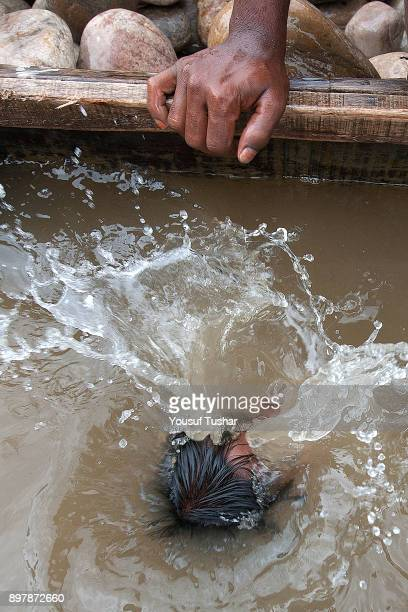 The Laborers are diving to collect stone at Jaflong Stone Quarry field The crystal clear water of the Piyain River which flows from India through...