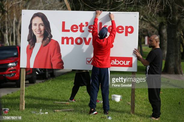 The Labour Party hoardings go up as media gather further down the strip to see new National Party leader Judith Collins help put up her new election...