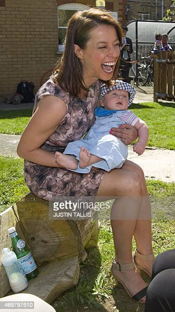 The Labour Party's prospective parliamentary candidate for Ashfield Gloria De Piero laughs as she holds a baby during a visit to Stockwell Gardens...