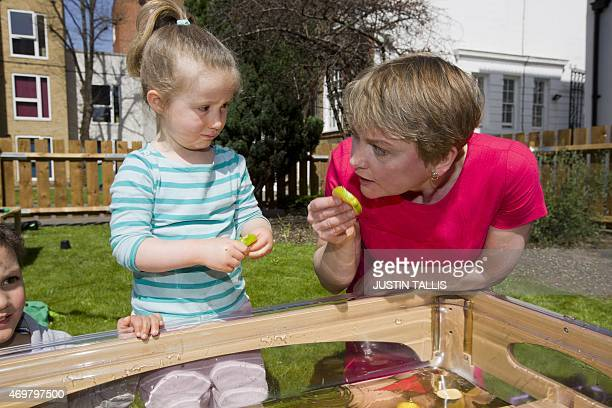 The Labour Party's prospective parliamentary candidate for Normanton Pontefract and Castleford Yvette Cooper holds a lime while talking with children...