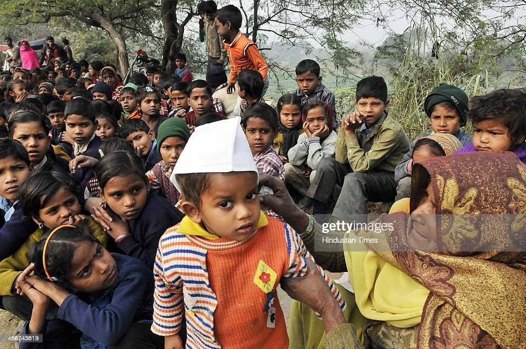 The lady adjusting the AAP cap worn by a child, as DDA officials came to demolish the Jhuggies along the Yamuna River near Mayur Vihar on December 20, 2013 in New Delhi, India.