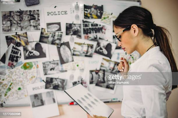 the lady detective is looking for clues about the case of a serious crime - - the hard work of a detective in the office - the detective in the office is working to gather evidence and clues in finding the killer - privateinvestigator stock pictures, royalty-free photos & images