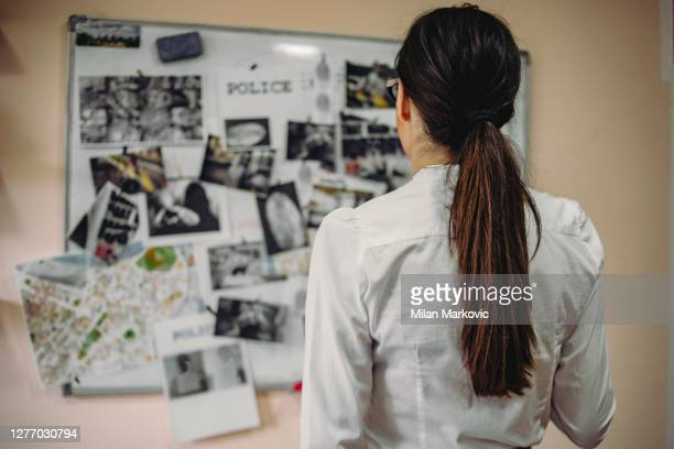 女性探偵は重大な犯罪の事件についての手がかりを探しています - - オフィスの探偵のハードワーク - オフィスの刑事は、殺人犯を見つける証拠と手がかりを収集するために取り組んでいま� - 警察署長 ストックフォトと画像