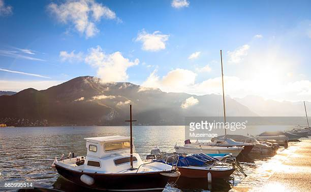 the lake, mountains and boats of annecy in the perfect morning day - lake annecy stock photos and pictures
