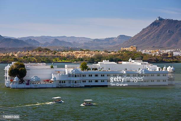 The Lake Palace Hotel Jag Niwas on island site on Lake Pichola with tourist boats arriving and leaving in Udaipur Rajasthan India