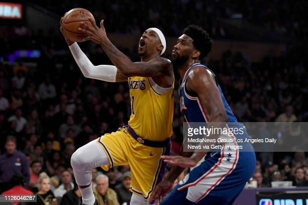 The Lakers' Kentavious CaldwellPope lays the ball up as the 76ers' Joel Embiid defends during their game at the Staples Center in Los Angeles Tuesday...