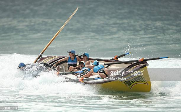 The Lakes Entrance crew hang on as they come through the breakers during their surf boat race during the surf lifesaving on day one of the 2009...