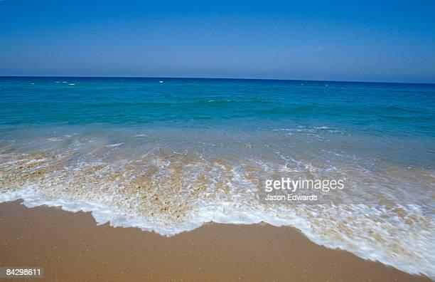 A deep blue sea and crisp waves lap the shoreline of the 90 Mile Beach