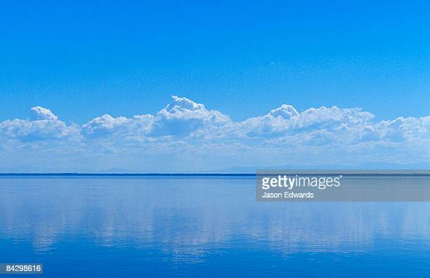 Light clouds reflected in a perfectly still lake surface in summer.