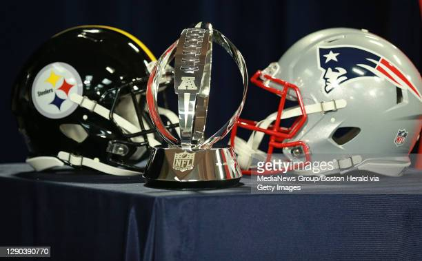 The Lamar Hunt AFC Championship trophy sits in front of Pittsburgh Steelers and New England Patriots helmets for a press conference at Gillette...