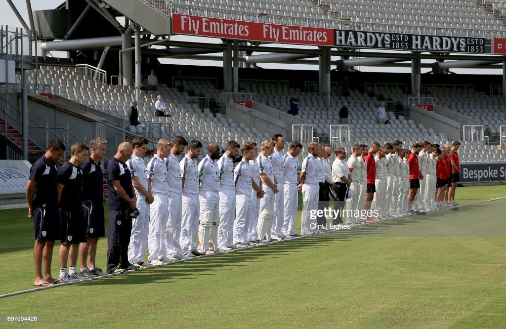The Lancashire and Hampshire teams hold a minute's silence before play in memory of the people who lost their lives in the Grenfell tower block fire in London during day one of the Specsavers County Championship game at Old Trafford on June 19, 2017 in Manchester, England.