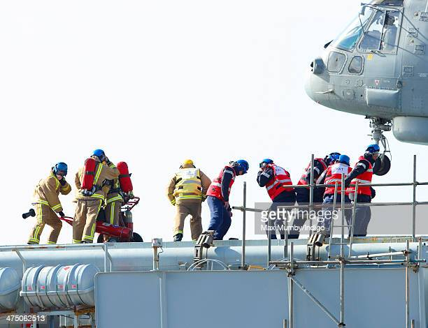 The Landing Crew and Firemen on the deck HMS Illustrious are buffeted by the downdraught of an inbound Royal Navy Merlin helicopter due to fly Prince...