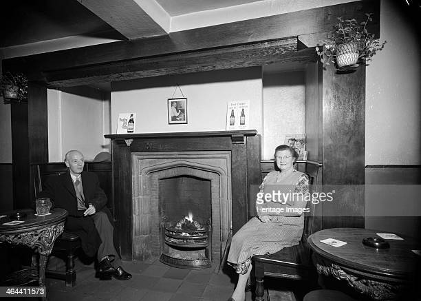 The landlady of the Greyhound Inn Penkhull StokeonTrent Staffordshire 1960 Photographed with a 'regular' with a pint on either side of the fire in...