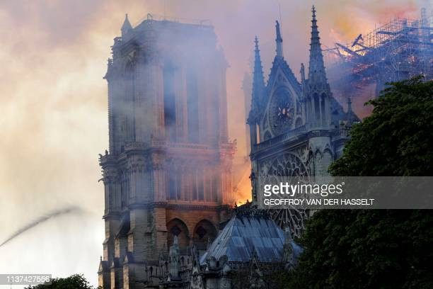 TOPSHOT The landmark NotreDame Cathedral is engulfed by flames in central Paris on April 15 2019 A huge fire swept through the roof of the famed...