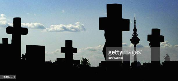 The landmark Spanish Television Tower stands in the background through crosses marking graves at La Almorena cemetary March 14 2004 in Madrid...