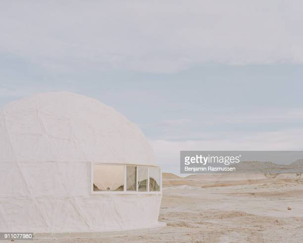 The landscape is reflected in the windows of the science lab at the Mars Desert Research Station on February 8 2017 'An exotic sunrise brought in a...