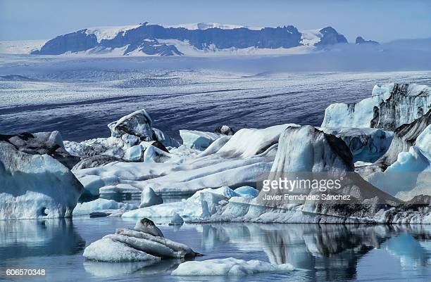 the landscape of ice blue icebergs floating on jokursarlon glacier lagoon, with glacier in the background. in southeast iceland, near the city of höfn. - breidamerkurjokull glacier stock photos and pictures