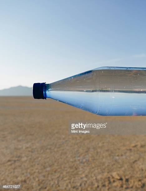 The landscape of the Black Rock Desert in Nevada. An essential element for survival. A bottle of water. Filtered mineral water. Sideways. The water level matching the horizon.