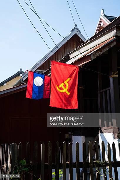 The Laotian flag and a flag bearing the communist hammer and sickle fly next to each other from a house in Luang Prabang Laos has a one party...