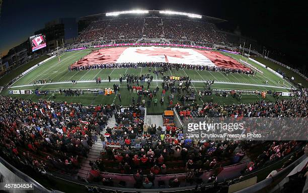 The largest Canadian flag in the world is unfurled to show solidarity after the terror attack in Ottawa earlier in the week prior to the game between...