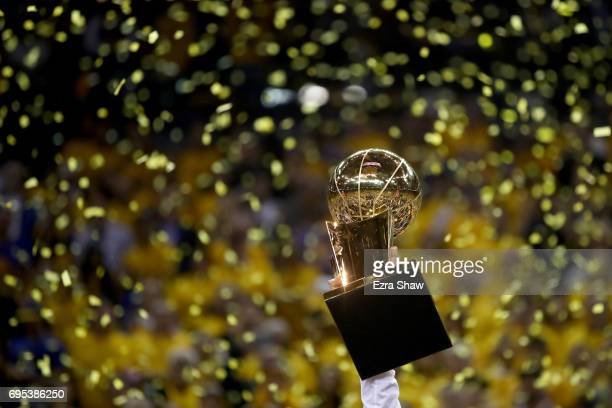 The Larry O'Brien Championship Trophy is held following the Golden State Warriors 129120 win over the Cleveland Cavaliers in Game 5 to win the 2017...