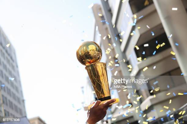 the Larry O'Brien Championship trophy is hoisted into the air during the Golden State Warriors Victory Parade on June 12 2018 in Oakland California...