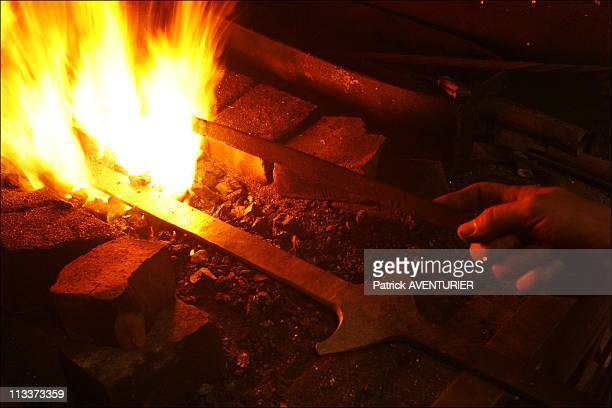 The 'Last DieHard' Edge Tool Maker Of Allassac In Allassac France On July 31 2008 The Second Empire blacksmith's bellows fans the fire during the...