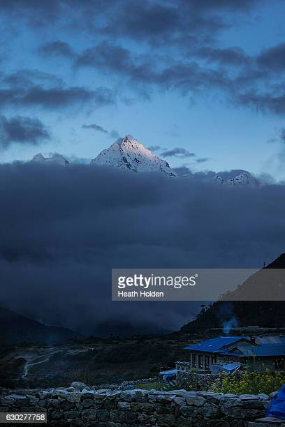 The last light illuminates the peak of Thamserku at sunset viewed from Thame village down the Bhote Khosi valley on September 23 2016 in Thame Nepal...