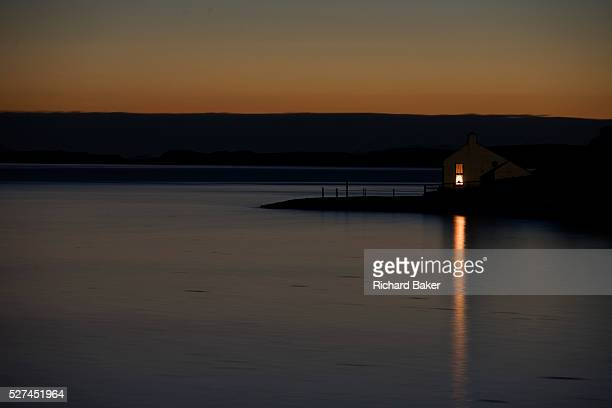 The last light of day fades on the still waters of Sgeir Nam Biast a bay overlooking Waternish Headland near Dunvegan northwest Isle of Skye Scottish...