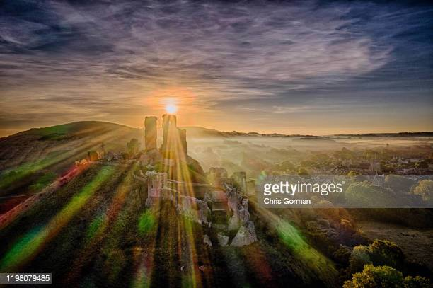 The last of the summer sun shines through the remains of Corfe Castle in Dorset on September 27 2018 in Corfe United Kingdom