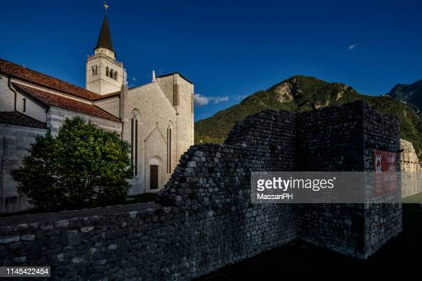 the last rays of sunshine lap the west facade of the cathedral of venzone - fortified wall stock photos and pictures
