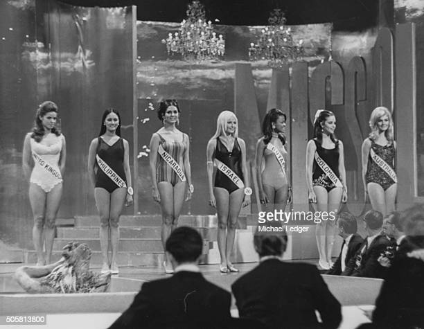 The last seven contestants in the 'Miss World' lined up on stage wearing swimsuits Kathleen Winstanley Arene Cecilia Amabuyok Margine Davidson...