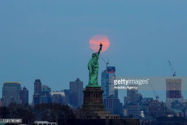 The last supermoon of 2019 'Super Worm Equinox Moon' rises behind the Statue of Liberty in New York United States on March 20 2019