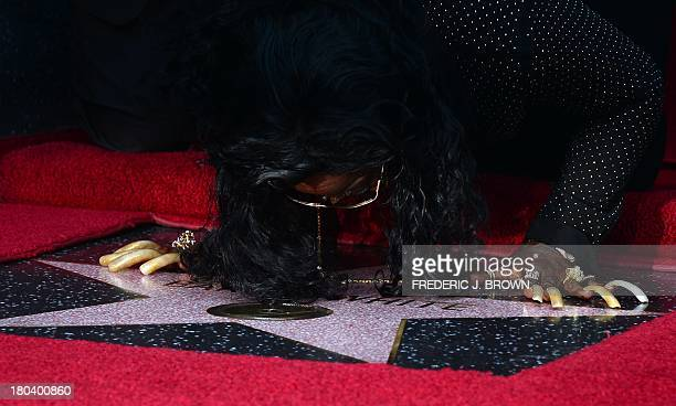 The late Barry White's wife Glodean White kisses her husband's posthumous star along the Hollywood Walk of Fame on September 12 2013 White who died...