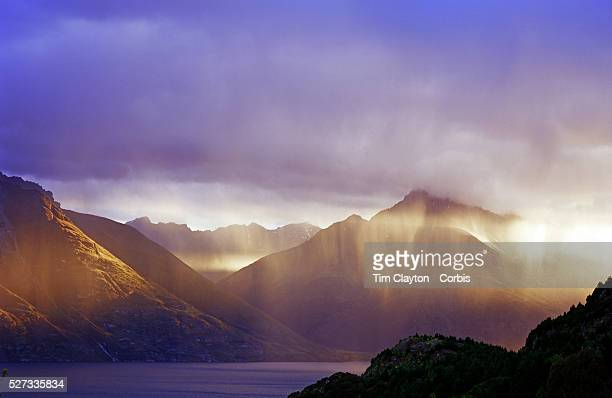 The late sun catches a rain shower on Lake Wakatipu Queenstown New Zealand Queenstown is nestled on the shores of the crystal clear waters of Lake...