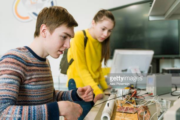 the late teenager boy and teenage girl working together in the engineering laboratory - physics stock pictures, royalty-free photos & images