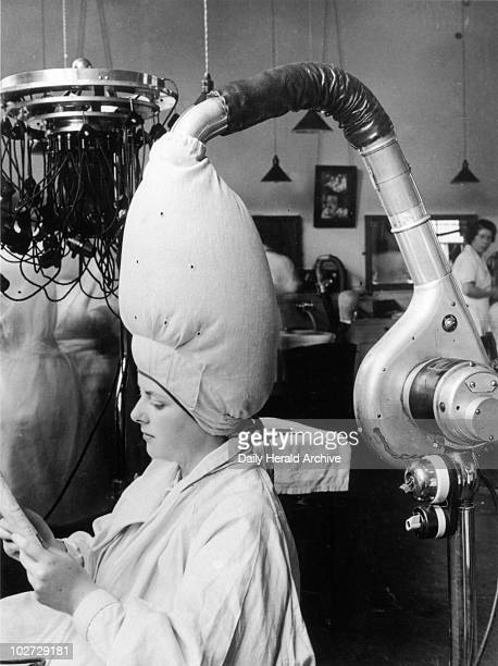 The latest hairdrying technology at a hairdressing school 8 July 1937 'A pupil who has just had a 'perm' undergoing the drying operation at the...