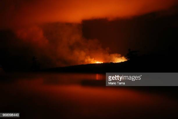 The latest Kilauea volcano activity illuminates the sky and is reflected off a vehicle on Hawaii's Big Island on May 14 2018 in Pahoa Hawaii The US...