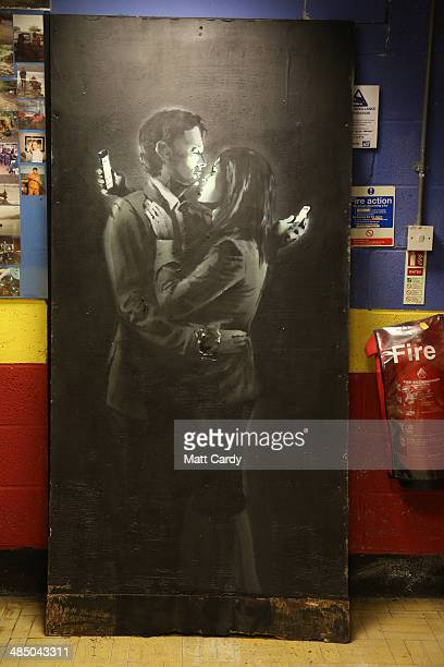 The latest officially confirmed Banksy artwork named Mobile Lovers featuring a man and a woman embraced and looking at their mobile phones sprayed...
