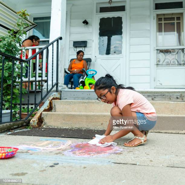 The Latino Mexican-American girl drawing with chalk at the porch of his house in Pennsylvania
