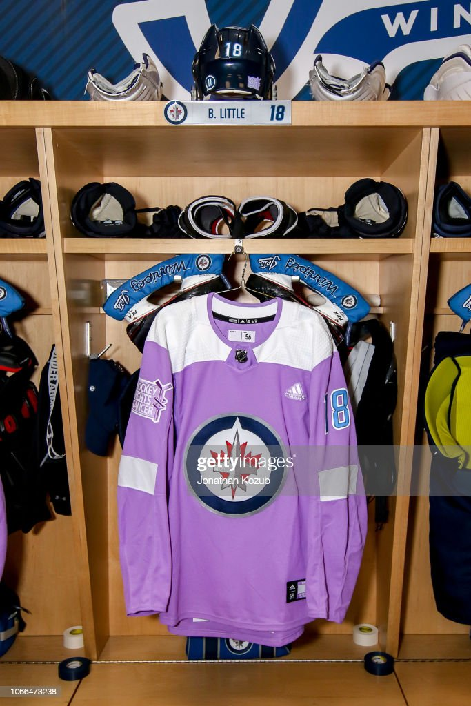 c9234ced274 The lavender jersey for Bryan Little of the Winnipeg Jets hangs in ...