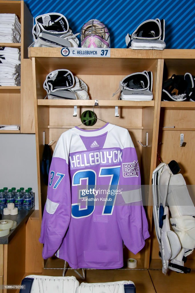 1582dd9c8bd The lavender jersey for Connor Hellebuyck of the Winnipeg Jets hangs ...