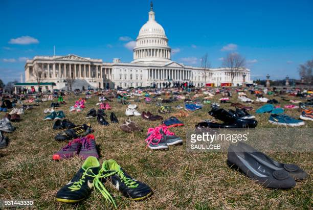TOPSHOT The lawn outside the US Capitol is covered with 7000 pairs of empty shoes to memorialize the 7000 children killed by gun violence since the...